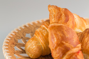 Croissants in wicker wooden plate