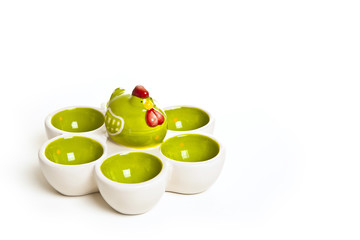 Easter egg cups with ceramic chicken on a white background