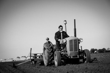Farmer in Old-fashioned tractor sowing crops at field, Black and white