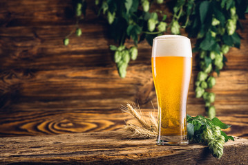 Glass of beer on old wooden table and wooden background