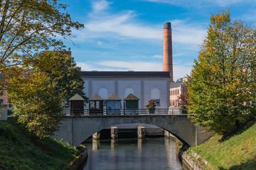 Kanal mit Brücke, Wehranlage, Bäume und Schornstein