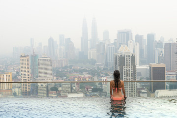 Beautiful woman in swimming pool watching the city