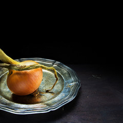 organic onion, served on a silver platter against a dark wood