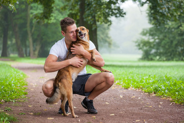 young man with dog in park