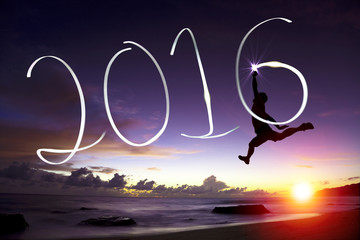 happy young man jumping  and drawing 2016 in the air