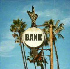 aged and worn vintage photo of bank sign with palm trees