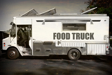 aged and worn vintage photo of black and white food truck