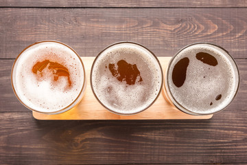 Assortment of beer glasses on a wooden background. Top view