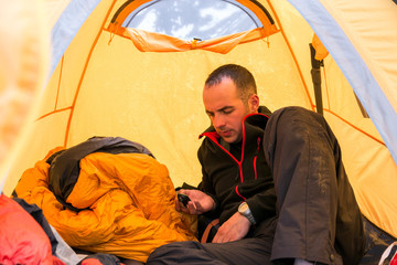 Climber inside Camping Tent Using Gadget Man lying on Sleeping Bag and Checking Oxygen Content in His Body