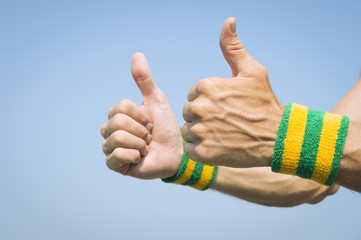 Brazilian athlete wearing Brazil colors wristbands holding two thumbs up against blue sky