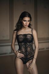Beautiful brunette girl posing in a black body lingerie
