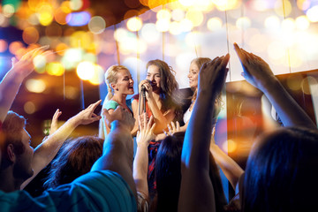 happy young women singing karaoke in night club