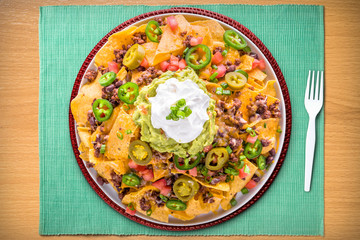 Large Plate of Supreme Nachos on a Turquoise Placemat