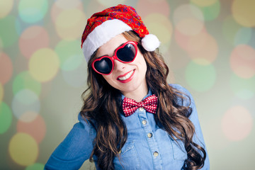 Young hipster girl in funny sunglasses and Christmas hat