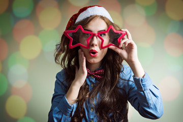 Surprised hipster girl in super size star glasses and santahat