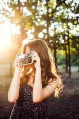 young caucasian female with vintage camera in park