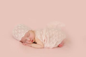 Neugeborenes Baby schläft auf dem Bauch zugedeckt mit einer Decke und mit Mütze