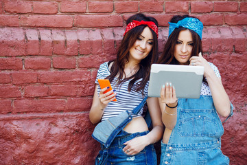 twins girls with tablet and smart phone