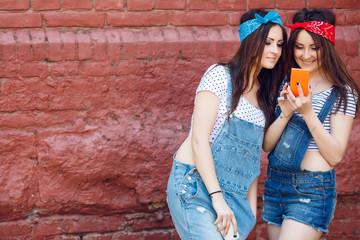 twins girls looking at orange smart phone.