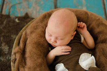 Liegendes Baby in einer Holzschale braun