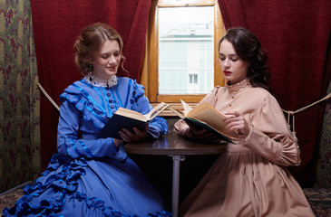 Two sisters in retro dress reading books in train compartment