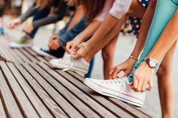 Group of teenage girls binding shoelaces