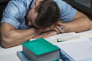 Tired doctor sleeping on desk