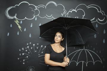 Giovane e bella ragazza si ripara con un ombrello da una pioggia disegnata