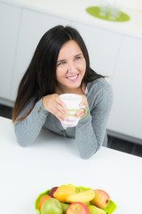 Frau lächelt mit Tasse in Küche