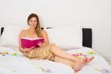 young woman reading a book in bed