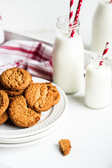 Oatmeal cookies with milk in jars on white wooden background