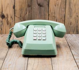 Retro green telephone on a wooden floor