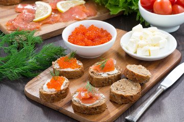 toasts with salted salmon and red caviar on wooden board