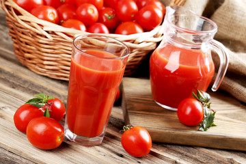 Fresh red tomatoes and tomato juice in glass on wooden table
