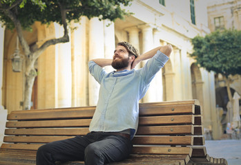 Relaxed man daydreaming on a bench
