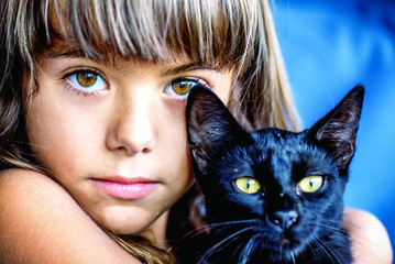 Portrait of a beautiful little girl holding a black cat