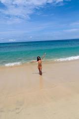 Girl in bikini stands on the beach