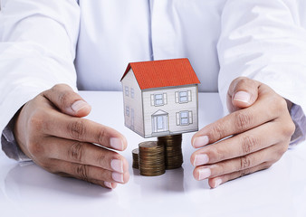 hand protection house paper on coins stack for mortgage loans co