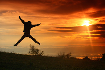 Young man jumps in the sunrise.
