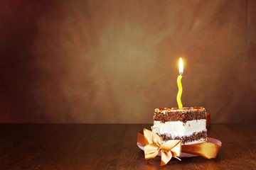 Piece of birthday chocolate cake with one burning candle against brown background
