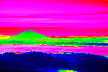Fantastic infrared scan of rocky landscape, pine forest with colorful fog, hot sunny sky above. Grunge background in amazing thermography colors.