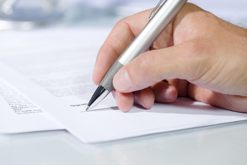 Close-up shot of hand signing a document