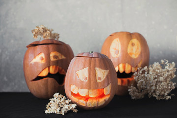 Three funny pumpkin for Halloween with flowers on a grey background