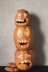 Three funny pumpkin for Halloween on a gray background