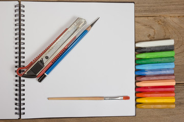 notebook and colorful crayons on wooden background.