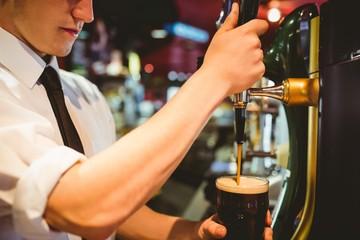 Spoed Foto op Canvas Bartender holding beer glass below dispenser tap