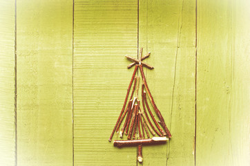 Christmas tree made from dry sticks on wooden, bright  background.