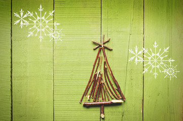 Christmas tree made from dry sticks on wooden, green background. Snow flaks image.