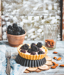 tartlets with cream cheese and blackberry on a light wooden.tabl
