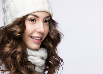 Beautiful girl with gentle makeup, curls and smile in white knit